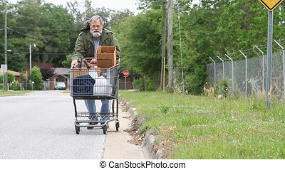 Homeless Man Pushing Cart - Homeless veteran pushes a...