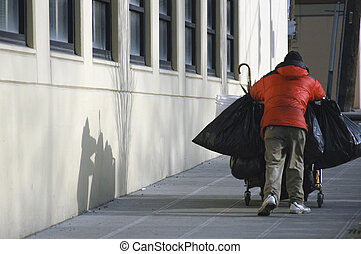 Homeless man pushing shopping cart of his belongings