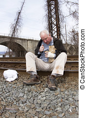 Homeless man sitting on edge of railroad tracks eating from...