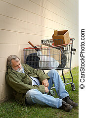 Homeless man leans against a wall sleeping with a grocery basket next to him containing his belongings.