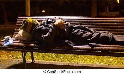 Homeless man sleeping on a park bench