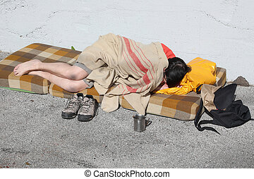 homeless man sleeps on a mattress on the street asking for alms