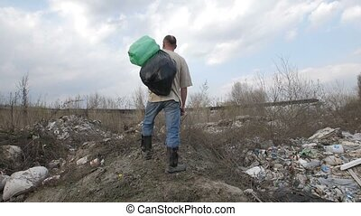 Homeless man standing on garbage hill at dump site -...