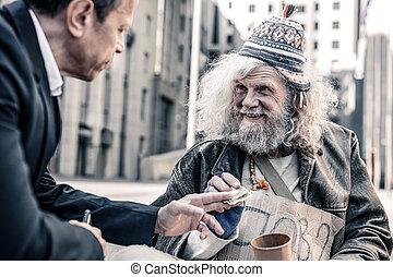 Beaming impressed grey-haired poor man thankfully receiving money