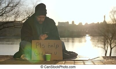 Homeless man using mobile phone while begging - Mature...