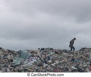Homeless man walking along the garbage heap in dump. Poverty. Environmental pollution.