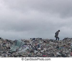 Homeless man walking along the garbage heap in dump.