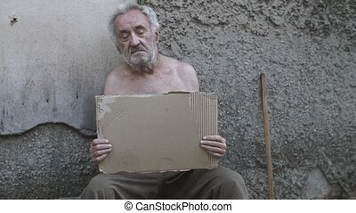 Homeless man with a sign asking for help - Homeless old man...