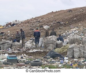 Homeless people with full bags in dump surrounded by rubbish.