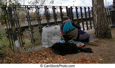 Homeless person asleep on a fence near river with bag of clothes near