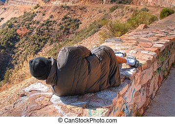 Homeless Person  - Homeless vagrant resting on a stone wall
