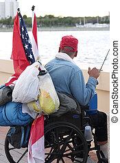 A homeless veteran with his belongings and an American flag, looking out over the ocean.