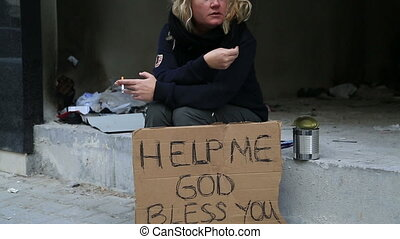 Homeless woman begging and smoking