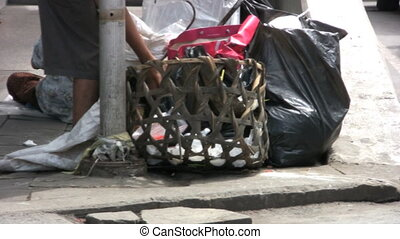 Homeless Woman Goes Through Garbage - An old Asian woman...