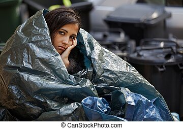 homeless young woman wrapped in plastic tarpaulin in cold weather