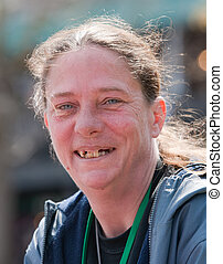 Homeless woman smiling with bad teeth. Outdoors during the daytime.