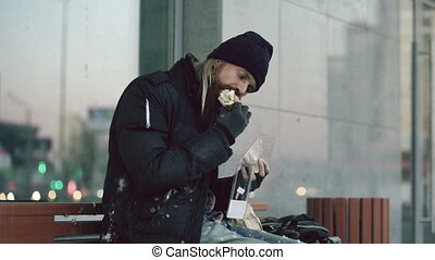 Homeless young man eating sandwich on bench at city street in evening
