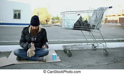 Homeless young man in dirty clothes drink alcohol sitting near shopping cart on the street at cold winter day