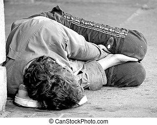 Homeless Youth on Street - A homeless youth sleeps on the...