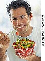 homem adulto meio, comer, salada