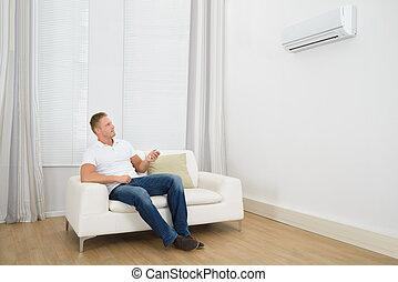 homem, ajustar, a, temperatura, de, condicionador ar
