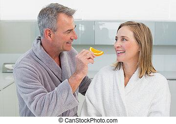 homem, alimentação, mulher, fatia alaranjada, em, cozinha