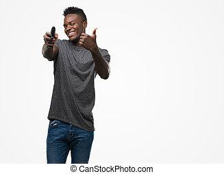 homem aponta cima, jovem, arma, americano, dedo, segurando, africano, mão, face sorridente, feliz