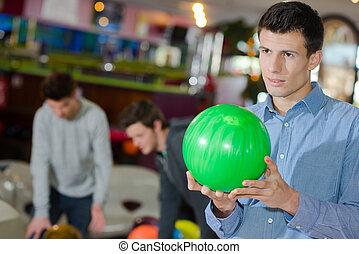 homem, bola, jovem, segurando, boliche