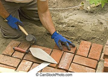 homem coloca, tijolo, pátio