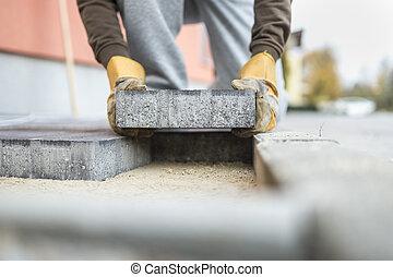 homem coloca, um, pavimentar, tijolo, colocar, aquilo, areia, fundação