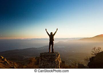 homem, com, mãos cima, montanhas, contra, sol