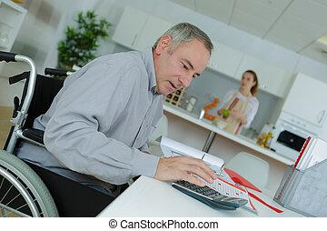 homem, em, cadeira rodas, fazendo, trabalho escritório, casa
