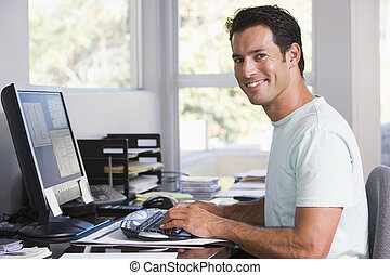 homem, em, escritório lar, usando computador, e, sorrindo