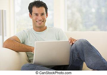 homem, em, sala de estar, usando computador portátil, sorrindo