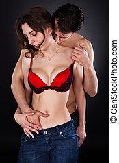 homem, enquanto, beijando, pescoço, calças brim, mão mulher, inserindo