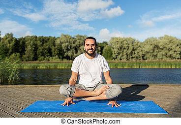 homem, fazer, ioga, em, escala, pose, ao ar livre