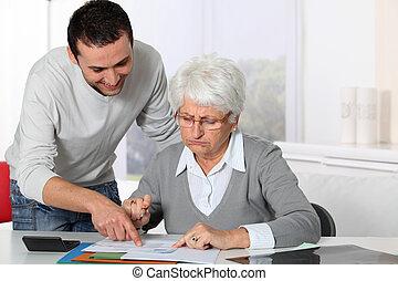 homem jovem, ajudando, mulher idosa, com, paperwork