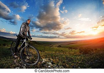 homem jovem, ciclismo, em, um, verão, prado, em, pôr do sol