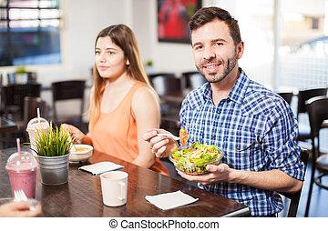 homem jovem, comer, salada, em, um, restaurante