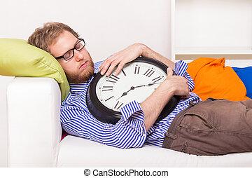 homem jovem, dormir, sofá, com, grande, relógio