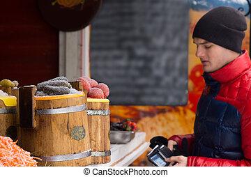 homem jovem, fazer, um, compra, em, um, ao ar livre, tenda