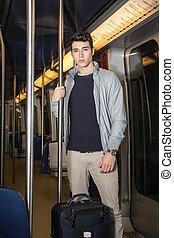 homem jovem, ficar, em, trem metrô, ir férias