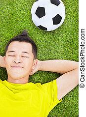 homem jovem, mentindo, ligado, um, prado, com, um, futebol