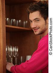 homem jovem, pôr, óculos, afastado, em, um, armário