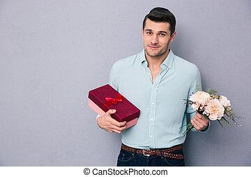 homem jovem, segurando, caixa presente, e, flores