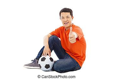 homem jovem, sentando, com, um, futebol, e, polegar cima