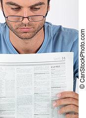 homem jovem, vidros desgastando, lendo jornal