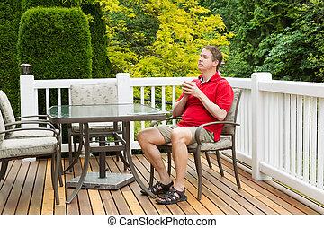homem maduro, descansar, cadeira, ligado, ao ar livre, pátio, com, xícara café