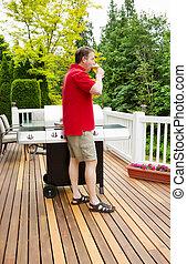homem maduro, relaxante, por, bebendo, cerveja, ligado, ao ar livre, pátio