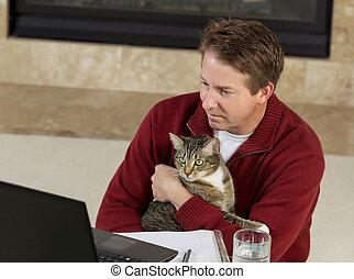 homem maduro, segurando, seu, animal estimação família, enquanto, trabalhando casa